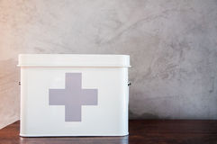 First aid kit box. Metal first aid kit box on wooden table royalty free stock photo