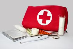 First aid kit. Thermometer, scissors, patch, dressing, foil and drug on the grey background Royalty Free Stock Image