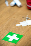First aid kit and green cross on a wooden surface Stock Photography