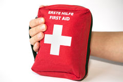 First aid kit with hand - english and german tittle Royalty Free Stock Image