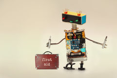 First aid kit and handyman service worker with screwdrivers. Fun toy robot, colorful head red blue light bulbs eyes royalty free stock images