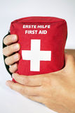 First aid kit with two hands - english and german tittle Stock Photos