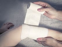 First aid at knee trauma. Close-up Stock Images