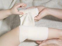 First aid at knee trauma. Close-up Stock Photos