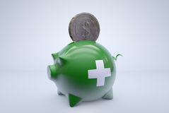 First aid piggy bank. A dollar coin is put into piggy bank, symbolizing financial aid Royalty Free Stock Images