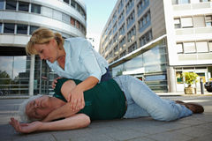 First Aid and recovery position. Passerby doing First Aid and helping senior women in recovery position Royalty Free Stock Photos