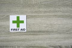 First aid sign on the wooden wall with space for adding text on the right side Royalty Free Stock Image