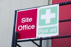 First aid site office sign on construction building door railing for workplace health and safety green cross. Uk stock image