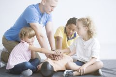 First aid training for children. Group of children exercising on a phantom during first aid training with instructor Stock Photography