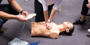 First Aid Training. Defibrillator CPR Practice. CPR training medical procedure workshop. Demonstrating chest compressions and use of AED automatic defibrillator royalty free stock photo