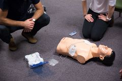 First Aid Training. Defibrillator CPR Practice. CPR training medical procedure workshop. Demonstrating chest compressions and use of AED automatic defibrillator stock photo