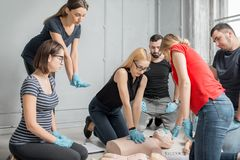 First aid training. Group of people learning how to make first aid heart compressions with dummies during the training indoors royalty free stock image