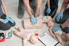 First aid training. Group of people learning how to make first aid heart compressions with dummies during the training indoors. Close-up view on the hands and stock image