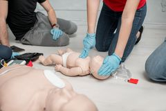 First aid training. Instructor showing how to make chest compressions on a baby dummy during the first aid training indoors royalty free stock image