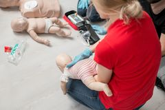 First aid training. Instructor showing how to safe a life when the baby is choked sitting during the first aid group training indoors Stock Photo