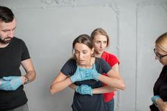 First aid training. Instructor showing how to safe a life when the human is choked standing during the fisr aid training indoors stock photo