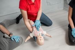 First aid training. Woman instructor showing how to make chest compressions on a baby dummy during the first aid group training indoors stock photography