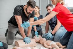 First aid training. Young women instructor helping to make first aid heart compressions with dummy during the group training indoors royalty free stock images