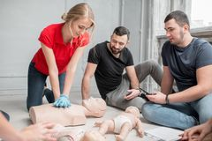 First aid training. Young women instructor showing how to make chest compressions with dummy during the first aid group training indoors stock photo