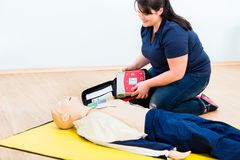 First aider trainee learning revival with defibrillator Royalty Free Stock Photos