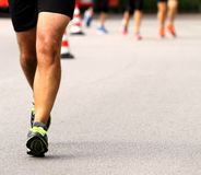 First athlete with muscular legs coming toward the finish line o Royalty Free Stock Image