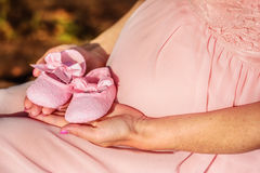 First baby girl shoes in a parent hands Royalty Free Stock Photography