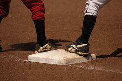 First Base. Opposing players wait on first base during a youth baseball game Stock Image