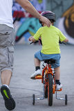 First bicycle ride. Father is running behind his young son who is on his first bike ride Stock Photos