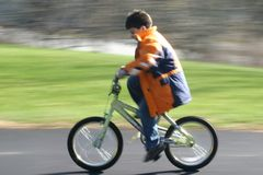 First bike solo in motion. Boy's first bike solo, caught in motion, on a driveway Stock Photography