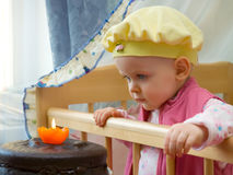 First birthday. The baby looks at the cake with a candle - it's first birthday Stock Photo
