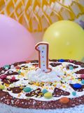 First birthday. Birthday cake with number one candle, balloons at background Royalty Free Stock Image