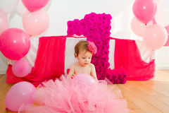 First birthday.Baby in fluffy pink skirt, with balloons and a bi. G Digits 1 Stock Images