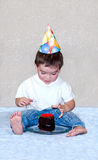 First Birthday boy with piece of cake Stock Photo