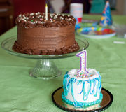 First Birthday Cakes. Happy birthday to a one year old! Two birthday cakes are on a green tablecloth. One cake is chocolate with a single candle. The smaller Stock Photos