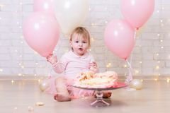 First birthday celebration - funny little girl with smashed cake. Over brick wall background with lights and colorful balloons Stock Photography