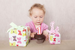 First birthday. Charming caucasian baby girl with presents and birthday cake on beige background Royalty Free Stock Images