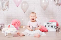 First birthday concept - funny dirty girl and smashed birthday cake with lights and balloons. First birthday concept - funny dirty baby girl and smashed birthday stock image