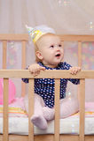 First birthday. Little girl sitting in a cardboard cap in a crib and looking delightedly at soap bubbles stock photography