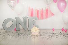 First birthday pink cake with flowers for little baby girl and decorations for cake smash. Big silver letters ONE. And pink and white baloons royalty free stock images