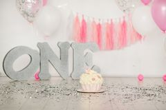 First birthday pink cake with flowers for little baby girl and decorations for cake smash. Big silver letters ONE and pink and whi. Te baloons stock image