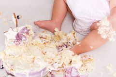 First birthday smash the cake. cream on legs. Close-up view.  Royalty Free Stock Photography