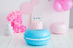 First birthday smash the cake. A pink cake stands on a large blue macaroon. First birthday Stock Image