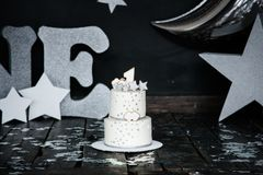 First birthday white cake with stars and candle for little baby boy and decorations for cake smash. Big silver letters ONE, silver. Stars and different balloons stock photos
