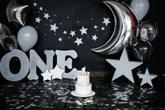 First birthday white cake with stars and candle for little baby boy and decorations for cake smash. Big silver letters ONE, silver. Stars and different balloons royalty free stock photo