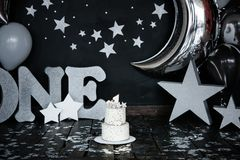 First birthday white cake with stars and candle for little baby boy and decorations for cake smash. Big silver letters ONE, silver. Stars and different balloons stock images