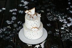 First birthday white cake with stars and one candle for little baby boy and decorations for cake smash. Black background royalty free stock image