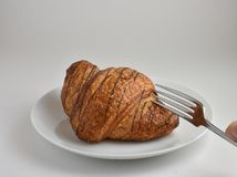 First bite showing a fork about to cut into a golden brown croissant Stock Photo