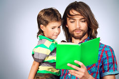 First book. Happy father reading a book to his adorable son stock photo
