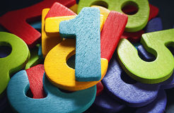 First. Bunch of wooden numbers, number one on top royalty free stock photo