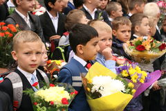 The first call. September 1, Knowledge Day in Russian school. Day of Knowledge. First day of school. Autumn bell blonde bouquets boys brick building call camera Royalty Free Stock Photography
